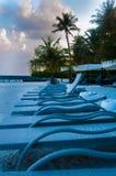 Esponga al sole le sedie dei letti tenute nella linea sulla spiaggia del mare Fotografia Stock Libera da Diritti