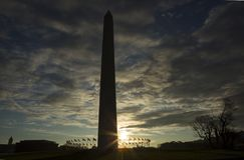 Esponga al sole muoversi dietro Washington Monument ha circondato dalle bandiere degli Stati Uniti contro cielo blu Fotografie Stock Libere da Diritti
