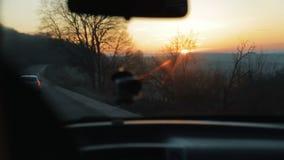 Esponga al sole splendere dal parabrezza, automobile che passa la strada principale, mettere a fuoco/che unfocusing, amici sunbri archivi video