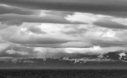 Esponga al sole splendere sulle montagne delle Svalbard in Norvegia dietro le nuvole Immagini Stock