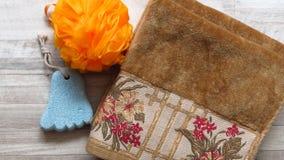A esponja alaranjada do banho, pé deu forma à pedra de polimento, toalha da cor do ocre fotos de stock royalty free