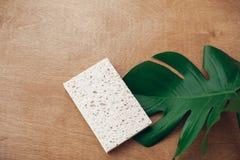 Esponja de celulose natural reusável no fundo de madeira com a folha verde do monstera Conceito zero do desperdício, configuração fotografia de stock royalty free