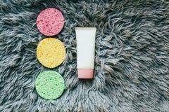 Esponja para el lavado de la cara y las botellas cosméticas fotografía de archivo libre de regalías