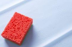 Esponja roja en superficie limpia azul con descensos del agua Concepto de pureza después de limpiar foto de archivo