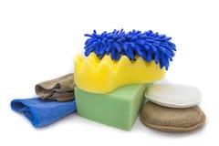 Esponjas amarelas, verdes e luvas azuis para o lavagem e a tela do microfiber Fotografia de Stock Royalty Free