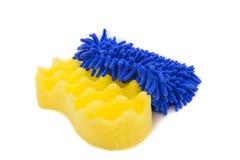 Esponjas amarillas y mitones azules para el coche que se lava Imagen de archivo libre de regalías