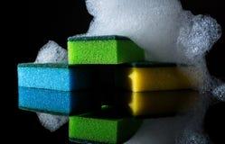 Esponjas coloridas com espuma e reflexão, bolhas, isoladas no preto Fotografia de Stock Royalty Free
