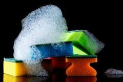 Esponjas coloridas com espuma e reflexão, bolhas, isoladas no preto Fotografia de Stock