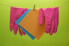 Esponjas de la cocina y guantes de goma que cuelgan en cuerda imagen de archivo