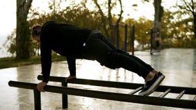 Esporte, aptidão, homem muscular novo que dá certo durante um exercício na rua O atleta caucasiano põe sobre fones de ouvido e filme
