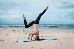Esporte, aptidão, ioga, povos e conceito da saúde - jovem mulher que faz o exercício do headstand no fundo da praia imagens de stock