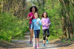 Esporte da família, mãe ativa feliz e crianças correndo na floresta imagens de stock