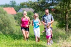 Esporte da família que corre através do campo fotografia de stock royalty free