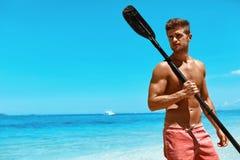 Esporte de água do verão Homem com a pá do caiaque da canoa na praia Fotografia de Stock Royalty Free