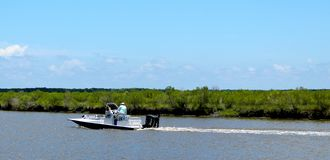 Esporte de barco abaixo do rio sob céus azuis fotos de stock