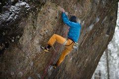 Esporte de inverno exterior Montanhista de rocha que ascensão um penhasco desafiante Escalada extrema do esporte imagem de stock