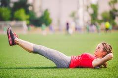 Esporte e saúde do tema A mulher caucasiano bonita nova que faz o aquecimento, aquecendo os músculos, os músculos abdominais malh imagem de stock royalty free