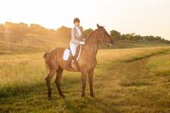 Esporte equestre O cavalo de equitação da jovem mulher no adestramento avançou o alargamento de Sun do teste Imagem de Stock
