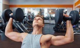 Esporte, halterofilismo, treinamento e conceito dos povos - homem novo com o peso que dobra os músculos homens que trabalham com  imagem de stock