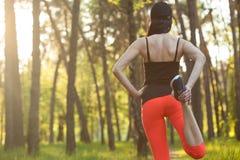 Esportes da menina esticar Corrida na floresta imagens de stock