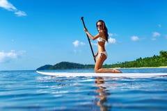 Esportes de água recreacionais Mulher que rema na placa de ressaca verão Fotografia de Stock