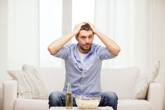 Esportes de observação do homem triste em casa Fotos de Stock Royalty Free