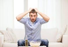 Esportes de observação do homem triste em casa Imagens de Stock Royalty Free