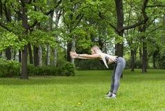 Esportes delgados da menina no parque, faz as curvaturas dianteiras fotos de stock royalty free