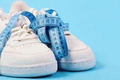 Esportes e conceito saudável do estilo de vida Ostente sapatas e a fita de medição azul no fundo ciano foto de stock