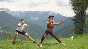 Esportes exteriores, povos, conceito da natureza - par que faz ocupas nas montanhas video estoque