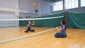 Esportes para deficientes motores Duas jovens mulheres que sentam-se no assoalho do gym e que jogam o voleibol Batendo a esfera video estoque