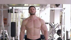 Esportes profissionais, indivíduo muscular que faz o exercício da força com pesos nas mãos durante o treinamento do poder no gym vídeos de arquivo