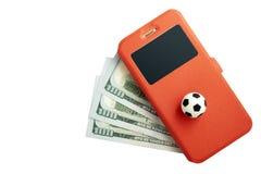 Esportes que apostam o conceito com um smartphone Uma bola do futebol e um telefone celular em uma mentira vermelha do caso em tr fotografia de stock royalty free