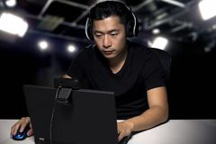 ESports Professional Competitive Gamer. Competitive asian male professional E Sports video gamer playing an FPS, or MMO game on a computer and streaming online royalty free stock photos