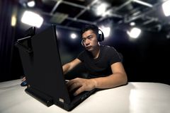 ESports Professional Competitive Gamer. Competitive asian male professional E Sports video gamer playing an FPS, or MMO game on a computer and streaming online royalty free stock photo