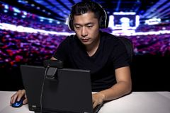 ESports Professional Competitive Gamer. Competitive asian male professional E Sports video gamer playing an FPS, or MMO game on a computer and streaming online Stock Photos
