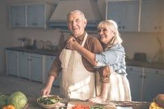 Esposa alegre que abraza a su marido en sitio del cocinero Foto de archivo libre de regalías