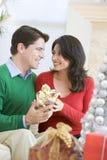 Esposa asombrosamente del marido con el regalo de Navidad Imagenes de archivo