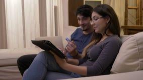 Esposa atrativa nova que senta-se em um sofá branco em casa que guarda o PC da tabuleta e que introduz dados do cartão de crédito video estoque