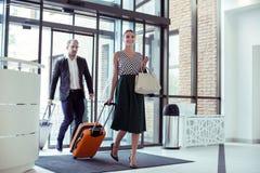 Esposa bonita que acompanha seu marido bem sucedido na viagem de negócios imagem de stock
