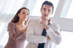 Esposa cariñosa preocupante que toma cuidado de su marido parado nervioso foto de archivo