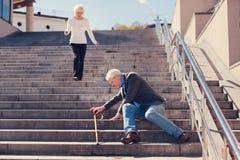 Esposa cariñosa que acomete abajo de las escaleras para ayudar al marido Fotos de archivo