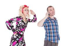 Esposa celosa que mira a su marido que usa el teléfono móvil fotografía de archivo libre de regalías