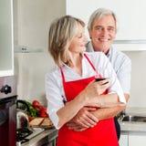 Esposa de abarcamiento del marido en cocina Imagenes de archivo