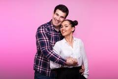 Esposa de abarcamiento del marido en fondo rosado Imagen de archivo