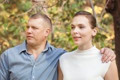 Esposa de abarcamiento del marido feliz en parque del otoño Fotografía de archivo libre de regalías