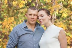 Esposa de abarcamiento del marido feliz en parque del otoño Imagen de archivo
