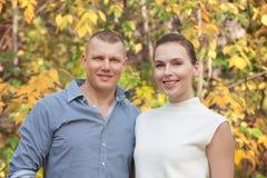 Esposa de abarcamiento del marido feliz en parque del otoño Imagen de archivo libre de regalías