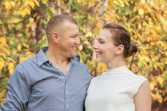 Esposa de abarcamiento del marido feliz en parque del otoño Fotografía de archivo