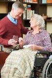 Esposa de ayuda del hombre mayor en silla de ruedas con la medicación Imágenes de archivo libres de regalías